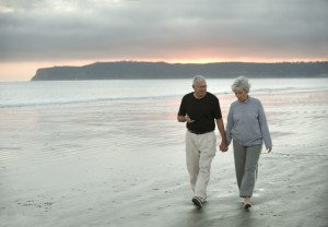 Senior couple walk on beach